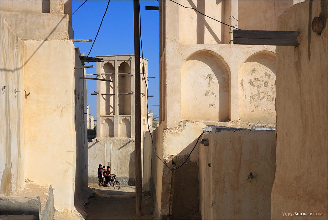 Iran - Мотоциклисты и ветряные башни бадгиры в рыбацкой деревне на острове Кешм