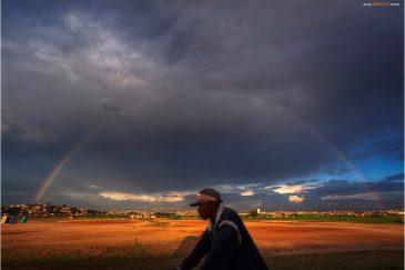 Радуга и велосипедист в радуге на окраине Антананариву