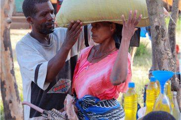 Муж помогает жене уложить мешок на голову по дороге с рынка
