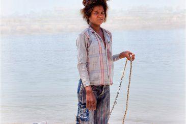 Девочка с собачкой на берегу Ганги в Варанаси. Индия
