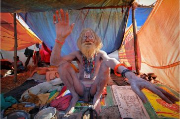 Престарелый баба благословляет прохожих на фестивале. Индия