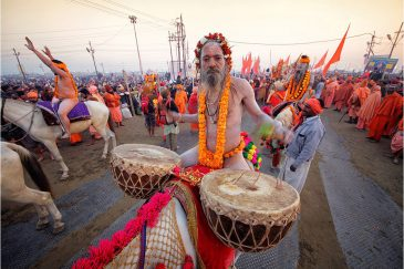 Барабанщики на лошадях возглавляют колонну аскетов на фестивале Кумбха Мела. Индия