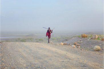 Воин из племени Масаи на дороге в северной Танзании